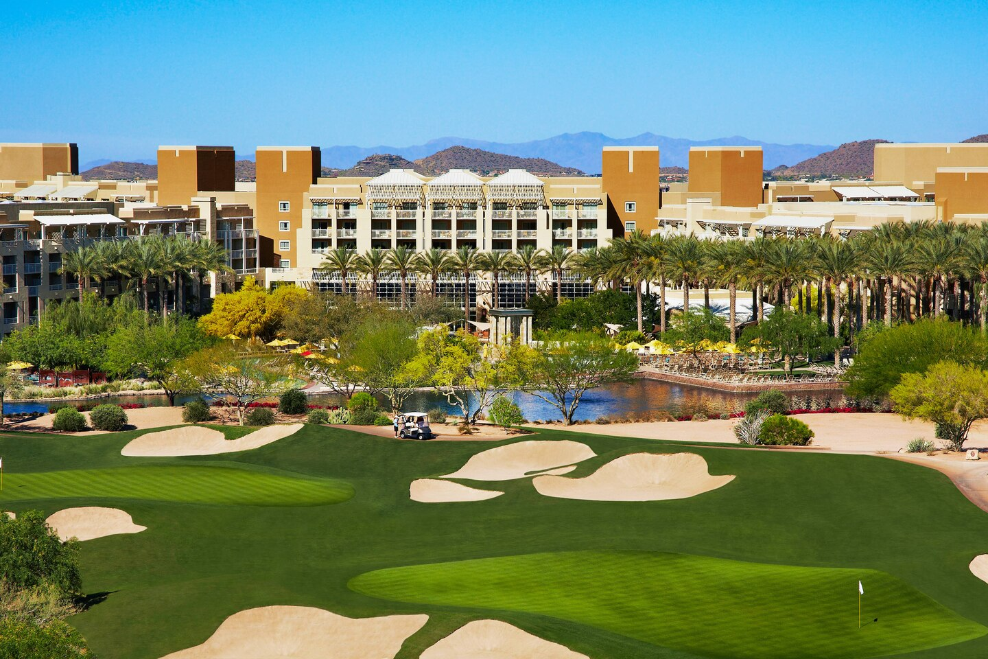 Photo of JW Marriott Phoenix Desert Ridge Hotel and Spa. Hotel is surrounded by trees and bushes, and golf course is in the foreground.