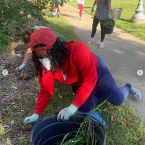Student holding a bucket with weeds and cleaning up community garden