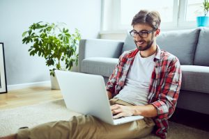 Young relaxed student working on laptop while sitting on floor at home