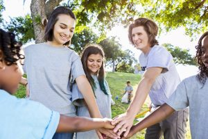 Happy volunteers put their hands together as a team